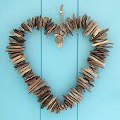 stock photo of driftwood  - Driftwood heart hanging on a blue oak wood background - JPG