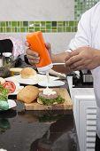 picture of hamburger  - Chef putting mayonnaise on the Hamburger bun  - JPG