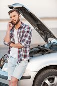picture of hoods  - Serious young man talking on the mobile phone while leaning a vehicle hood - JPG
