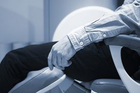 stock photo of cat-scan  - Patient in fully open MRI CAT Scan scanning arm elbow forearm hand and fingers - JPG