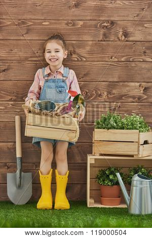 Cute child girl caring for her plants. Cute little girl holding garden tools standing in the backyard. Spring concept, nature and care.