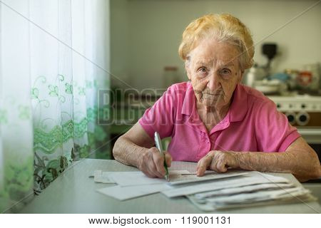 The old woman fills out utility bills sitting in the kitchen.