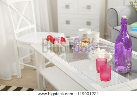 Low table with purple bottle, sweets and two cups in living room