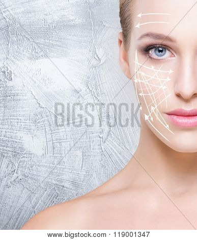 Half face portrait of attractive girl with beautiful blue eyes and arrows on face over concrete background. Face lifting concept.