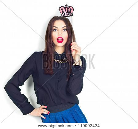 Surprised sexy model Gil holding funny crown on stick isolated on white background. Joyful young fashion woman with bright make up, red lips and nails