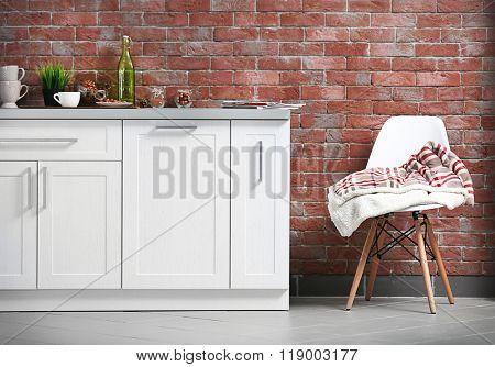 Modern kitchen furniture against brick wall background
