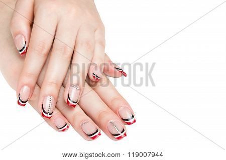 French manicure - beautiful manicured female hands with red black and white manicure with rhinestone