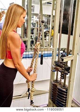 Girl in profile workout on bicep curl machine with rope in sport gym.