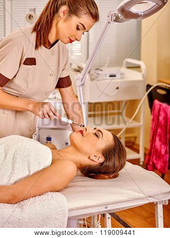 Young woman receiving electric galvanic face spa massage luxuriating at beauty salon.
