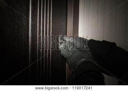 man's hand in a glove opening the door