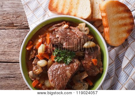 Rustic Beef Bourguignon In A Bowl On A Table Close-up. Horizontal Top View