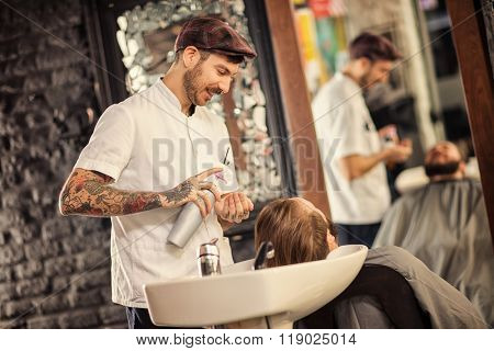 Hairstylist washing head of man with beard in barbershop
