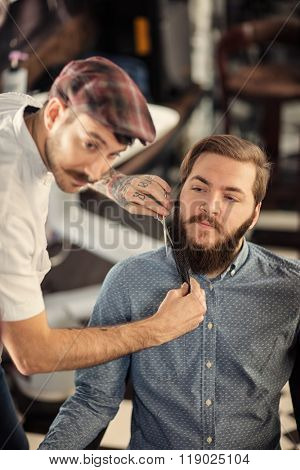 Hairdresser shaving with scissors and combs of satisfied client