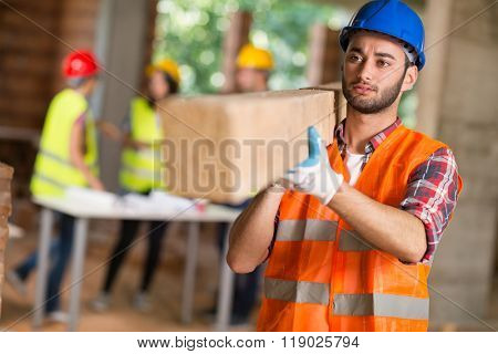 Young worker bring construction beam at work