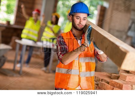 Young construction worker bring timber at building site