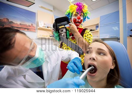 Young girl on dental treatment with crazy clown holding chainsaw behind
