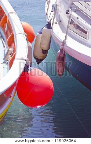 Close Up Of Boats Standing Besides Each Other With Buoys