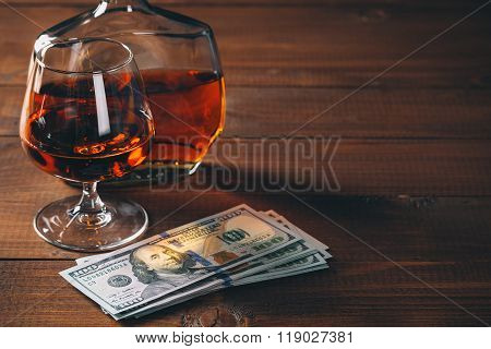 Glass With Cognac And Bottle, With Wad Of Money On The Wooden Table.