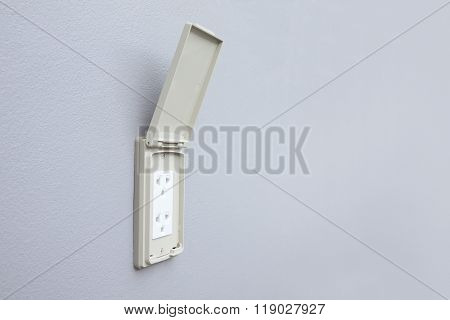 Outdoor electrical outlet with cover on cement wall.