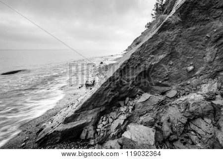 Wild beach, sea and cliff erosion in winter. Black and white. Conceptual composition dividing image into light and dark halves.