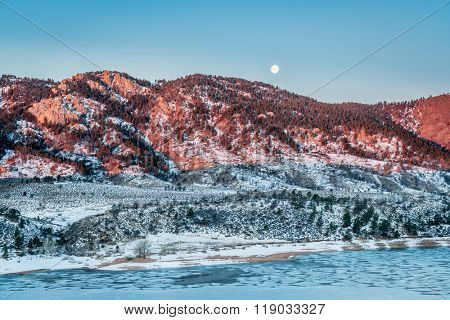 Moon setting over Arhturs Rock lit by sunrise with Horsetooth Reservoir covered by ice, Fort Collins, Colorado