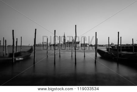 The Church of San Giorgio Maggiore from the main Venice waterfront showing wooden posts in the foreground. Taken in black and white