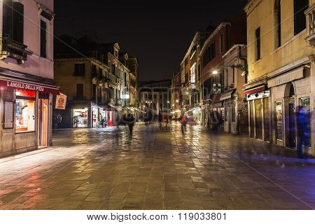 VENICE ITALY - 13TH MARCH 2015: Buildings and businesses along Rio Terà S. Leonardo in Venice at night. The blur of people walking can be seen.