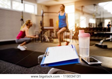 Gym details, women exercising, clipboard, water bottle, smart ph