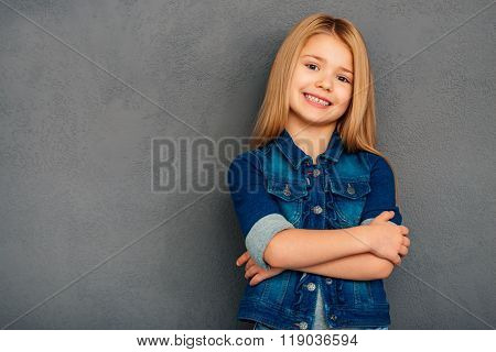 Little cutie. Cheerful little girl holding arms crossed and looking at camera with smile while standing against grey background ** Note: Soft Focus at 100%, best at smaller sizes