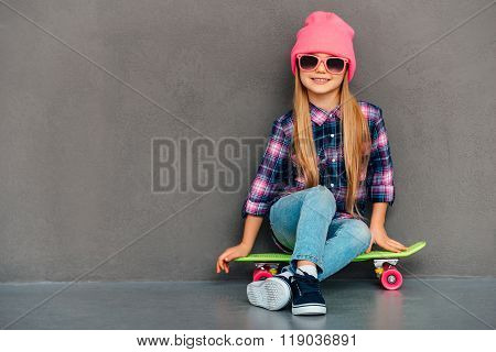 Carefree cutie with skateboard. Full length of cheerful little girl looking at camera with smile while sitting on skateboard against grey background