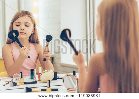 Which brush is better? Cute little girl choosing one of two make-up brushes while sitting at the dressing table
