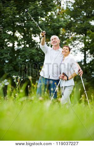 Happy senior couple hiking in a forest in nature in summer