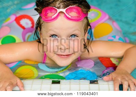Funny little girl swimming in a pool