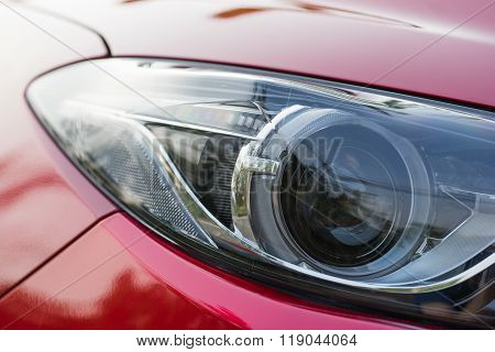 Xenon Projector Headlight Of A Red Car