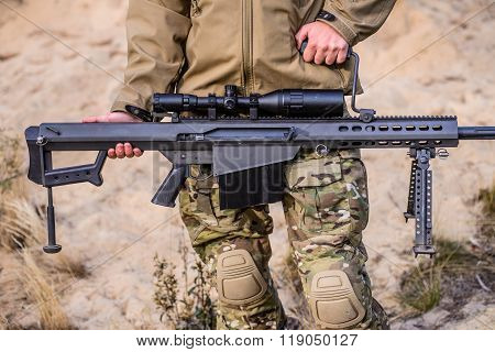 Man In Uniform Holding Large Caliber Sniper Rifle