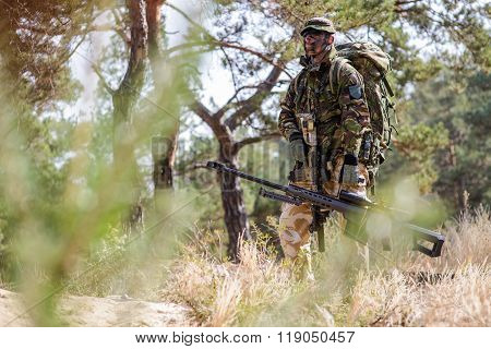 Armed Soldier With Sniper Rifle In The Forest