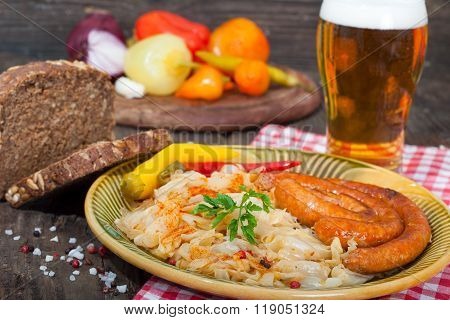 Grilled sausages with sauerkraut, bread and glass of beer