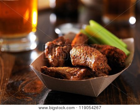 barbecue chicken wings with celery in basket on restaurant table