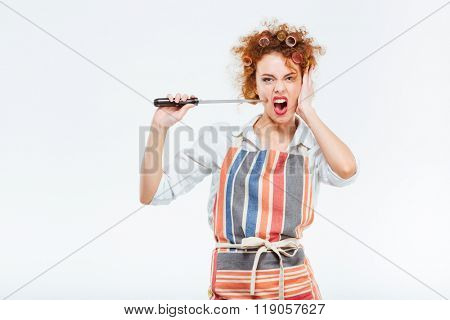 Curly redhead young housewife with rollers in striped apron holding and playing with knife over white background