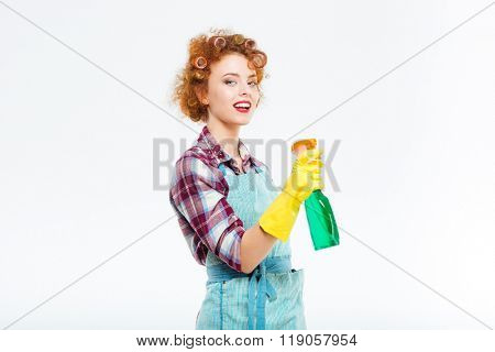 Smiling cute redhead young housewife in rubber gloves holding cleaning bottle and spraying over white background