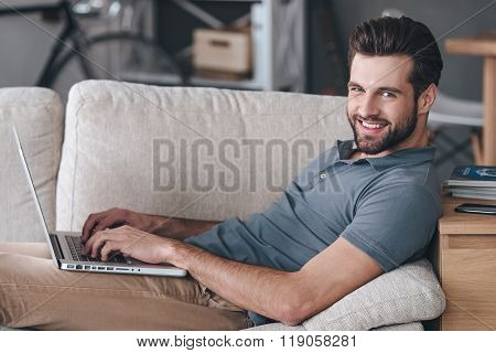 Cheerful blogger. Side view of handsome young man using his laptop and looking at camera with smile while sitting on the couch at home