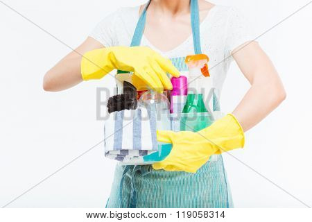 Closeup of cleaning supplies in plactic box holded by young housewife in blue kitchen apron over white background