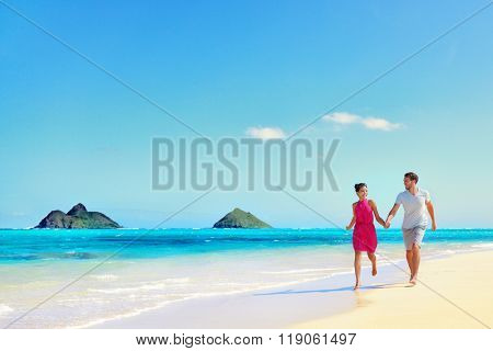 Hawaii vacation couple walking relaxing on white sand and pristine turquoise ocean water on Hawaiian beach Lanikai, Oahu island, USA. Holiday background with blue sky copy-space for travel concept.