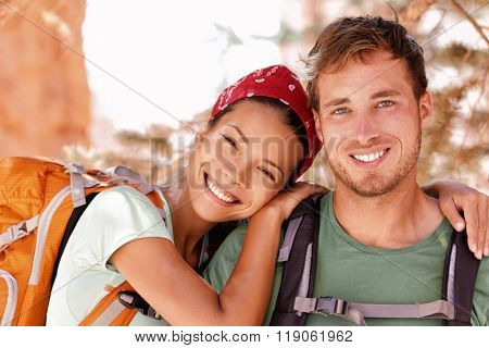 Happy young hikers backpacking on summer travel. Portrait of two friends teenagers or student couple