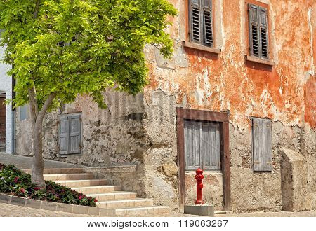 aged red house on historic street in Italy