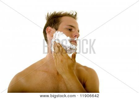 Young male putting shaving cream on his face