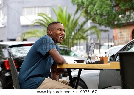 Young African Man With A Laptop At Cafe