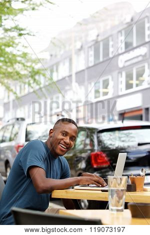 Young African Man At Cafe With Laptop