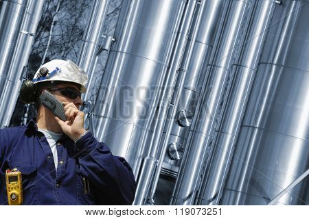 refinery worker with giant gas pipes in the background