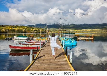 Jasper National Park, Pyramid Lake. Solar cold morning. On boat moorage elderly woman performs yoga, pose